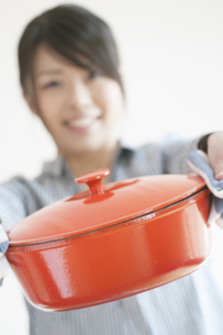 鍋を持ち微笑む女性の写真素材 [FYI04547815]