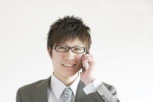 スマートフォンで電話をするビジネスマンの写真素材 [FYI04547829]