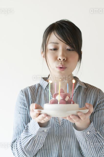 ケーキのろうそくの火を吹き消す女性の写真素材 [FYI04547830]