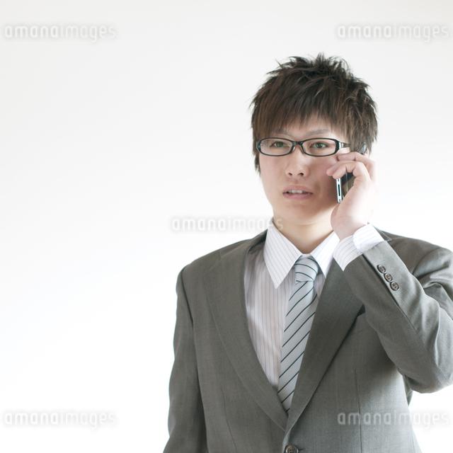 スマートフォンで電話をするビジネスマンの写真素材 [FYI04547839]