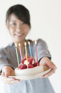 ケーキを持ち微笑む女性の写真素材 [FYI04547860]