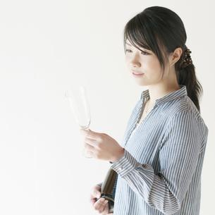 ボトルとシャンパングラスを持ち微笑む女性の写真素材 [FYI04547862]