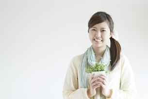 植物を持ち微笑む女性の写真素材 [FYI04547866]