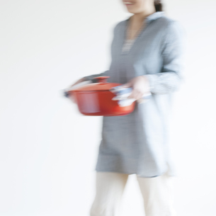 鍋を運ぶ女性の写真素材 [FYI04547870]
