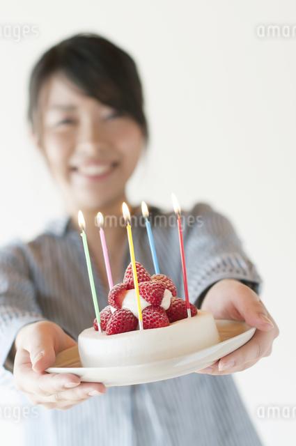 ケーキを持ち微笑む女性の写真素材 [FYI04547882]