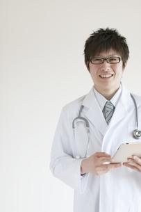 タブレットPCを持ち微笑む医者の写真素材 [FYI04547885]