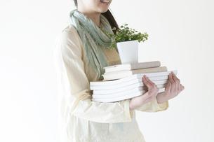 本と植物を運ぶ女性の写真素材 [FYI04547917]
