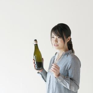 ボトルとシャンパングラスを持ち微笑む女性の写真素材 [FYI04547952]