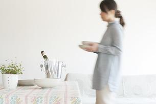 食器を運ぶ女性の写真素材 [FYI04547959]