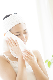 タオルで顔を拭く女性の写真素材 [FYI04547973]