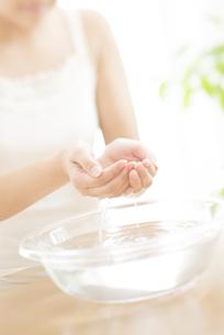 洗面器の水をすくう女性の手元の写真素材 [FYI04547985]
