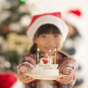 クリスマスツリーの前でケーキを差し出す女の子の写真素材 [FYI04547988]