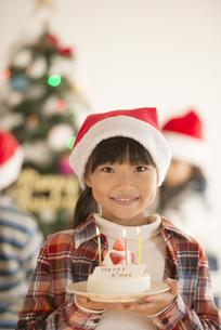 クリスマスツリーの前でケーキを持つ女の子の写真素材 [FYI04547989]