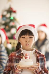 クリスマスツリーの前でケーキを持つ女の子の写真素材 [FYI04547990]