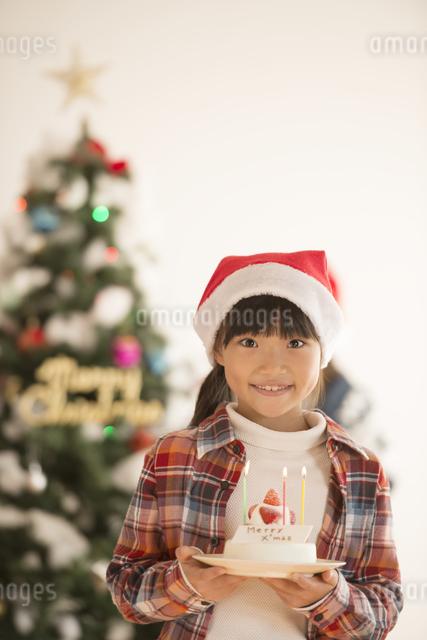 クリスマスツリーの前でケーキを持つ女の子の写真素材 [FYI04547991]