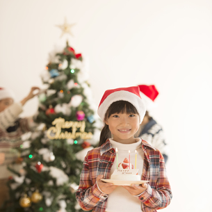 クリスマスツリーの前でケーキを持つ女の子の写真素材 [FYI04547993]