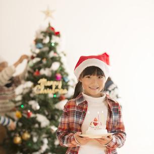 クリスマスツリーの前でケーキを持つ女の子の写真素材 [FYI04547994]