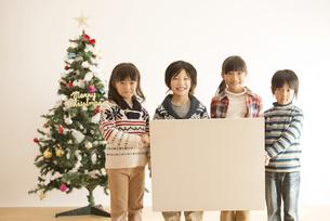 メッセージボードを持つ子供達とクリスマスツリーの写真素材 [FYI04548028]