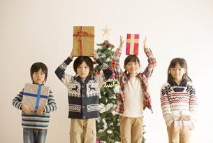 プレゼントを持つ子供達とクリスマスツリーの写真素材 [FYI04548034]