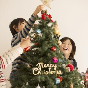 クリスマスツリーの飾り付けをする子供達の写真素材 [FYI04548047]