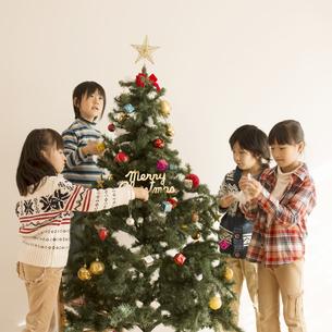 クリスマスツリーの飾り付けをする子供達の写真素材 [FYI04548050]