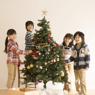 クリスマスツリーの飾り付けをする子供達の写真素材 [FYI04548054]