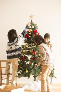クリスマスツリーの飾り付けをする子供達の写真素材 [FYI04548059]