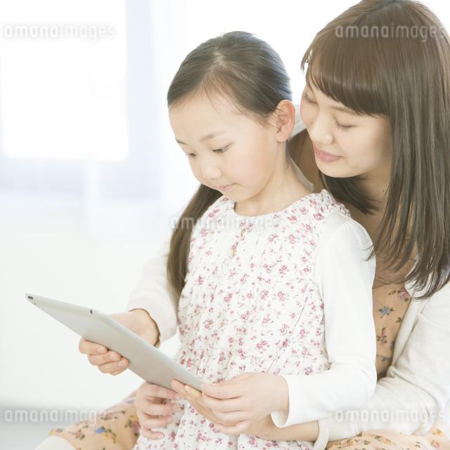 タブレットPCを見る親子の写真素材 [FYI04548064]