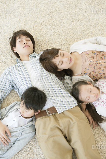 父親に寄りかかり眠る家族の写真素材 [FYI04548086]