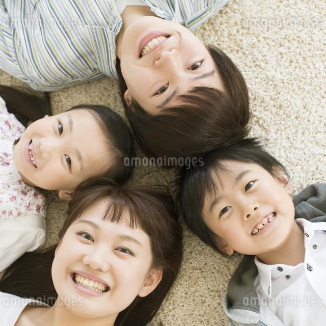 床に寝転び微笑む家族の写真素材 [FYI04548093]