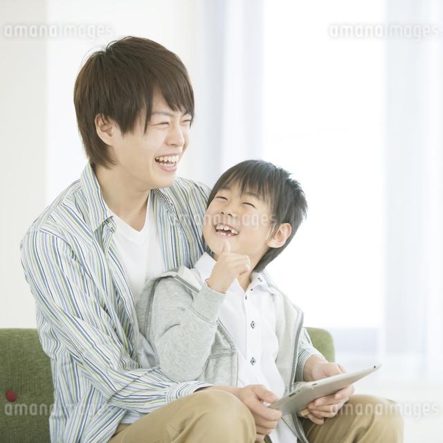 タブレットPCを見る親子の写真素材 [FYI04548096]