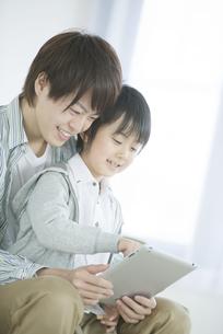 タブレットPCを見る親子の写真素材 [FYI04548097]