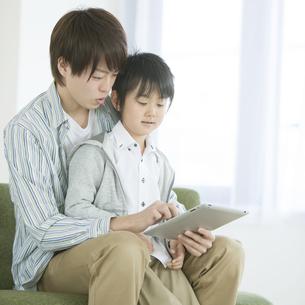 タブレットPCを見る親子の写真素材 [FYI04548098]