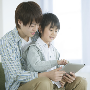 タブレットPCを見る親子の写真素材 [FYI04548099]