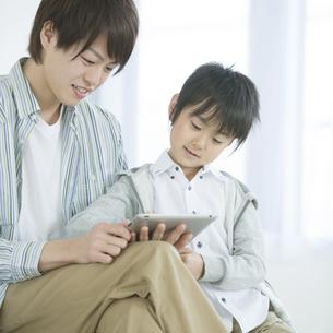 タブレットPCを見る親子の写真素材 [FYI04548100]