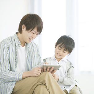 タブレットPCを見る親子の写真素材 [FYI04548101]