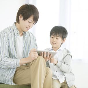 タブレットPCを見る親子の写真素材 [FYI04548103]