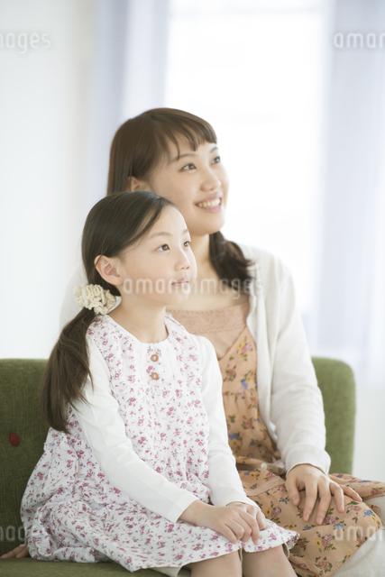 ソファーに座り微笑む親子の写真素材 [FYI04548114]