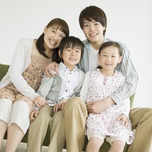 ソファーに座り微笑む家族の写真素材 [FYI04548121]