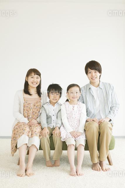 ソファーに座り微笑む家族の写真素材 [FYI04548129]