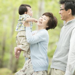 新緑の中で赤ちゃんをあやす祖父母の写真素材 [FYI04548260]
