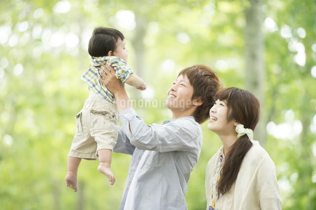 新緑の中で子供をあやす両親の写真素材 [FYI04548264]