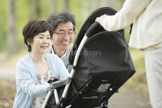 ベビーカーに乗る孫を見て微笑む祖父母の写真素材 [FYI04548272]