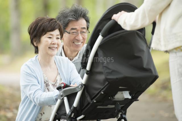 ベビーカーに乗る孫を見て微笑む祖父母の写真素材 [FYI04548273]