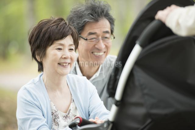 ベビーカーに乗る孫を見て微笑む祖父母の写真素材 [FYI04548274]