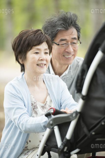 ベビーカーに乗る孫を見て微笑む祖父母の写真素材 [FYI04548275]