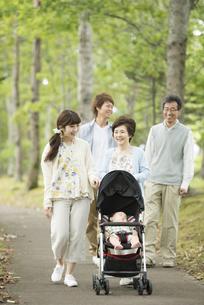 新緑の中で散歩をする3世代家族の写真素材 [FYI04548279]