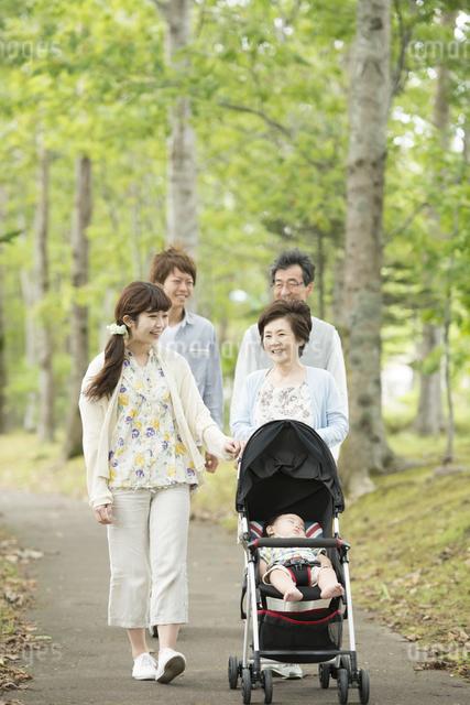 新緑の中で散歩をする3世代家族の写真素材 [FYI04548280]