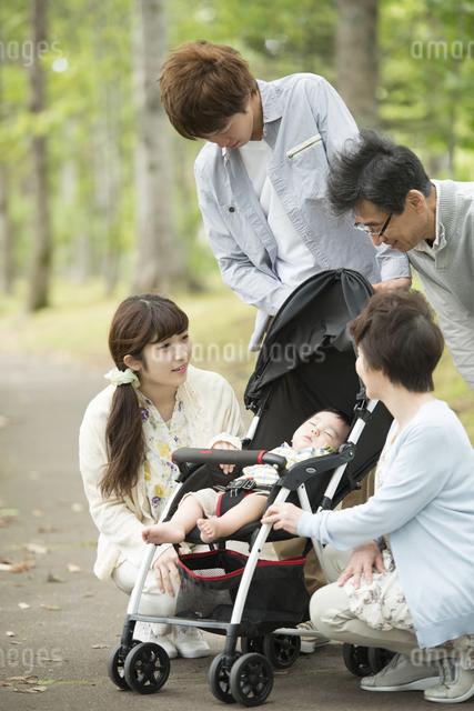ベビーカーで眠る赤ちゃんを見守る家族の写真素材 [FYI04548281]