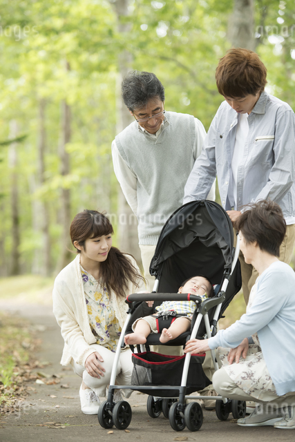 ベビーカーで眠る赤ちゃんを見守る家族の写真素材 [FYI04548284]